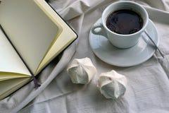 Kaffee mit Eibischen und einem Notizbuch im Bett lizenzfreie stockfotos