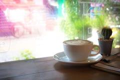Kaffee mit einem Kaktus und Dateien innerhalb eines Gebäudes mit Gekritzeln Stockbild
