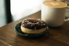 Kaffee mit einer Milch und einem Donut lizenzfreies stockbild