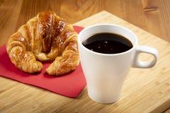 Kaffee mit Hörnchen auf dem Tisch Lizenzfreies Stockbild