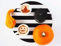 Kaffee mit Halloween-Belag, Kürbise und Franzosen drücken auf einen Hintergrund von Schwarzweiss-Streifen Stockbild
