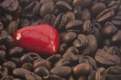 Kaffee mit Herzen - Kaffeebohnen im Hintergrund Lizenzfreies Stockfoto