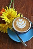 Kaffee mit Innerbild und -blumen. Stockfoto