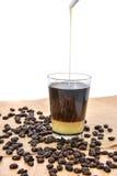 Kaffee mit Kondensmilch und Kaffeebohne Stockfotografie