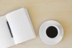 Kaffee mit leerem Notizblock und Stift auf Holztisch Stockbilder