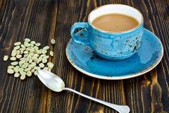 Kaffee mit Milch, Cappuccino in einer blauen Retro- Schale mit grünem Coff Stockbild