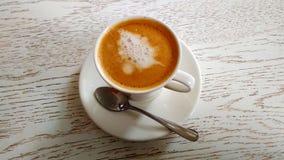 Kaffee mit Milch in einem weißen Becher auf einer weißen Tabelle stockbild