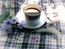 Kaffee mit purpurroten Blumen und trockenem Gras blüht auf dem Tisch mit der Morgensonne Abbildung der roten Lilie Stockbild