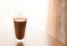 Kaffee-Morgen auf dem Tisch mit Sonnenlicht durch Spitzengardine Lizenzfreies Stockbild