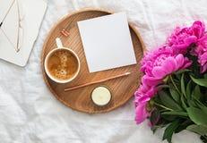 Kaffee, rosa Pfingstrosen und leeres Papier auf dem Bett stockbilder