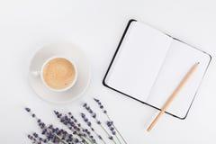 Kaffee, sauberes Notizbuch und Lavendel blühen auf weißer Tabelle von oben Frauenarbeitsschreibtisch Gemütliches Frühstück Modell lizenzfreie stockbilder