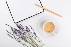 Kaffee, sauberes Notizbuch und Lavendel blühen auf weißer Tischplatteansicht Frauenarbeitsschreibtisch Gemütliches Frühstück Mode Stockfotos