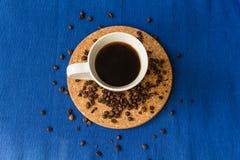 Kaffee Schale schwarzer Kaffee und verschüttete Kaffeebohnen Süßes Hörnchen und ein Tasse Kaffee im Hintergrund Stockbilder