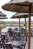Kaffee-Terrasse durch den Fluss mit Holzstühlen und Tabellen stockbilder