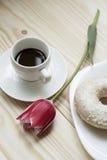 Kaffee, Tulpe und Donut auf einem hölzernen Hintergrund Lizenzfreie Stockfotografie