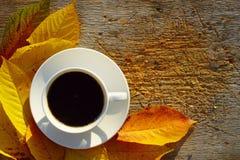 Kaffee und Autumn Leaves On Wood stockfoto