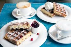 Kaffee und belgische Waffeln auf einer blauen Tabelle Lizenzfreie Stockfotografie