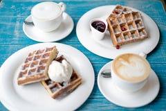 Kaffee und belgische Waffeln auf einer blauen Tabelle Stockbilder