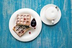 Kaffee und belgische Waffeln auf einer blauen Tabelle Lizenzfreies Stockfoto