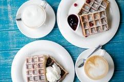 Kaffee und belgische Waffeln auf einer blauen Tabelle Stockbild
