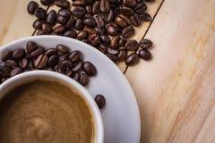 Kaffee und Bohnen auf einem Holztisch Lizenzfreie Stockbilder