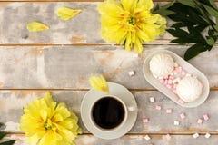 Kaffee und Eibische auf hölzerner Hintergrundzusammensetzung mit Blumen Lizenzfreies Stockfoto
