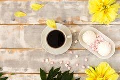 Kaffee und Eibische auf hölzerner Hintergrundzusammensetzung mit Blumen Lizenzfreie Stockbilder