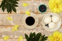 Kaffee und Eibische auf hölzerner Hintergrundzusammensetzung mit Blumen Stockfotografie