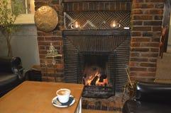 Kaffee und ein angenehmer Kamin Lizenzfreie Stockbilder