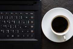 Kaffee und ein Notizbuch und ein Stift und Gläser auf einem schwarzen Hintergrund Stockbild