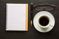 Kaffee und ein Notizbuch und ein Stift und Gläser auf einem schwarzen Hintergrund Stockbilder