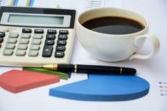Kaffee und ein Taschenrechner über Finanzdokumenten Lizenzfreie Stockfotos