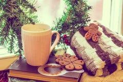 Kaffee und eine Strickjacke auf dem Buch am Fenster Falsche Stimmung stockfotos