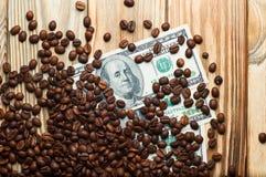 Kaffee und Geld auf einem Holztisch Einkommen auf Kaffee Stockbild