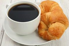 Kaffee und Hörnchen auf weißem hölzernem Hintergrund Lizenzfreies Stockfoto