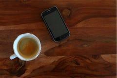 Kaffee und Handy auf dem Holztisch Lizenzfreies Stockfoto