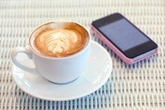 Kaffee und Handy auf weißer Tabelle im Café Lizenzfreies Stockfoto