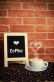 Kaffee und Kaffeebohnen mit Kreidebrett Lizenzfreie Stockbilder