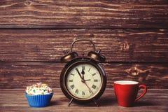 Kaffee und kleiner Kuchen mit Wecker Lizenzfreie Stockfotografie