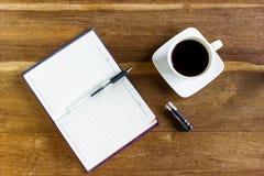 Kaffee und Notizblock, Arbeitsplatzgeschäftsmann Lizenzfreies Stockfoto