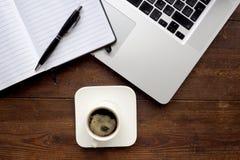 Kaffee und Notizblock mit Computer auf einem hölzernen Schreibtisch Lizenzfreie Stockfotos