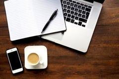 Kaffee und Notizblock mit Computer auf hölzernem Schreibtisch Stockfoto