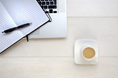 Kaffee und Notizblock mit Computer auf weißem Hintergrund Lizenzfreie Stockfotografie