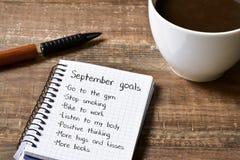 Kaffee und Notizblock mit einer Liste von September-Zielen lizenzfreie stockbilder
