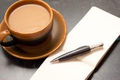 Kaffee und Notizbuch Stockfotos