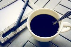 Kaffee und Notizbuch auf Holztisch Stockfotografie