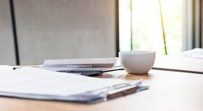 Kaffee und Papier auf dem Schreibtisch Stockbild