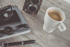 Kaffee und persönliche Einzelteile auf dem Desktop Lizenzfreie Stockbilder