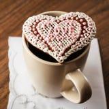 Kaffee und Plätzchen in Form von Herzen auf einer Serviette mit Stickerei in Form von Herzen Stockbilder