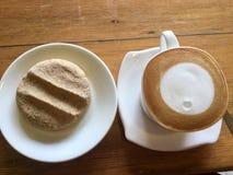 Kaffee und Plätzchen Lattemondkunst stockfotografie